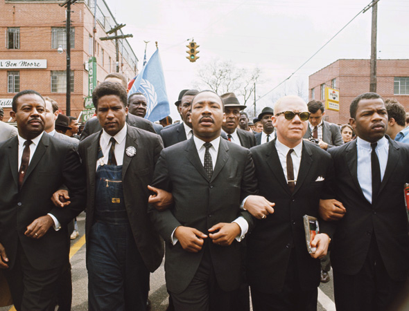 Martin Luther King Jr marching with linking arms